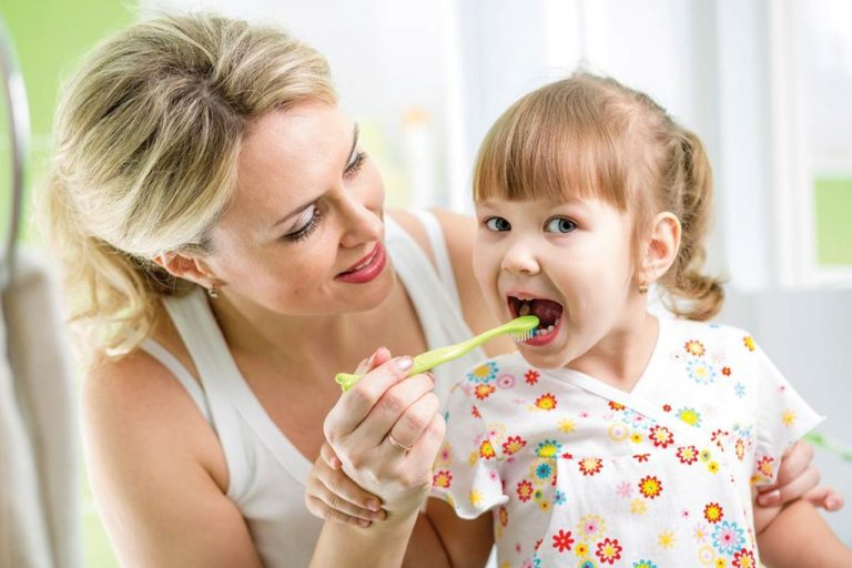 Mother with daughter brushing tooth