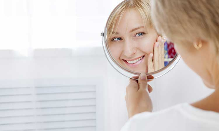 women looking into the mirrior checking her face | Botox and Cosmetic Dermal Fillers